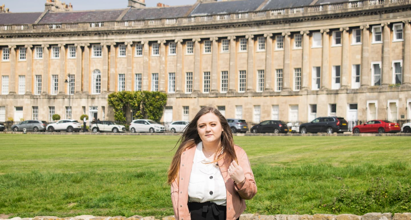 photo of me in front of Royal Cresent (a row of terraced houses that curves around a green area)